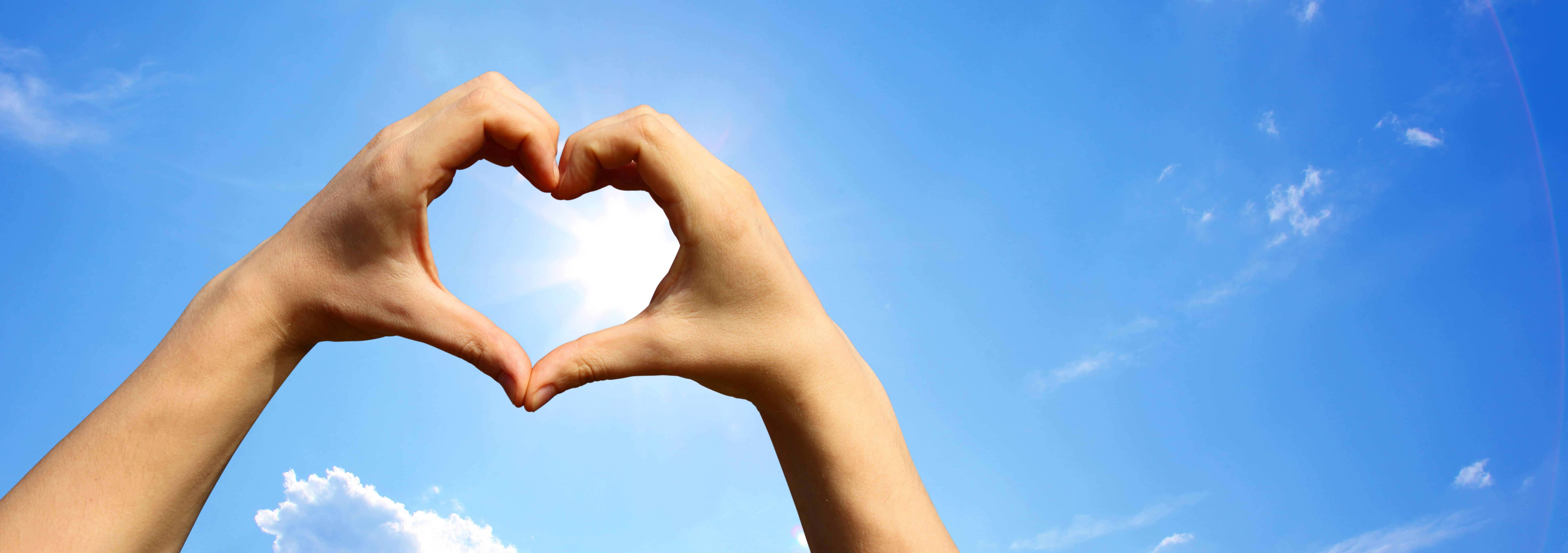 bild på hand som formar hjärta mot solen